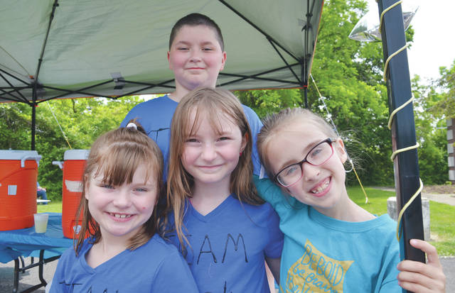 Trista Rowe (center), brother Timmy Rowe, and friends Natalie Brown and Autumn Metro grin from ear to ear as legions of well-wishers stop by their lemonade stand in support of wounded Amherst police officer Eugene Ptacek.