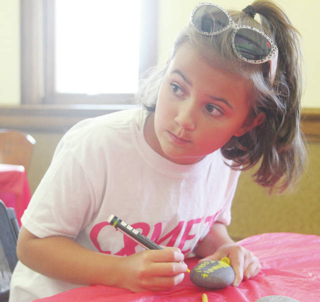 Ava Dutton of Amherst paints her rock.