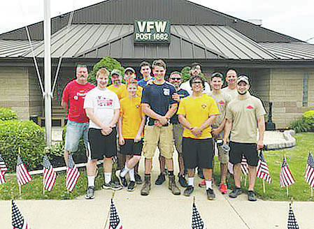 Members of Amherst's VFW Post 1662 and Boy Scouts Troop 427 celebrate a job well done after cleaning up the VFW building's exterior.