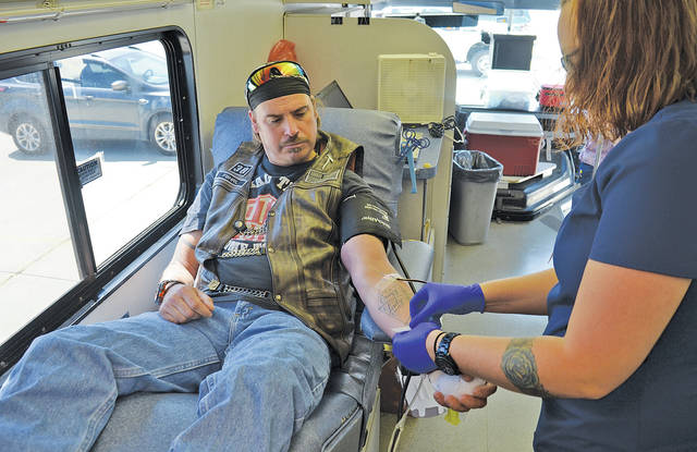 "Shawn Clawson rolls up his sleeve and phlebotomist Danielle Bashak slides a needle into his vein July 19 at a LifeShare blood drive in honor of Amherst police officer Eugene ""J.R."" Ptacek."