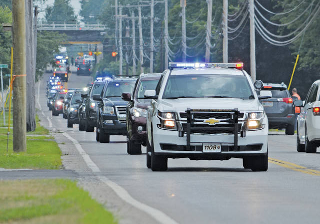 A stream of police vehicles representing nearly every community in Lorain County surges down North Lake Street to the Amherst police station, escorting Ptl. Eugene Ptacek home.