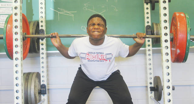 Oberlin eighth-grader Tavion Thomas receives encouragement from upperclassmen as he works through a squat repetition.