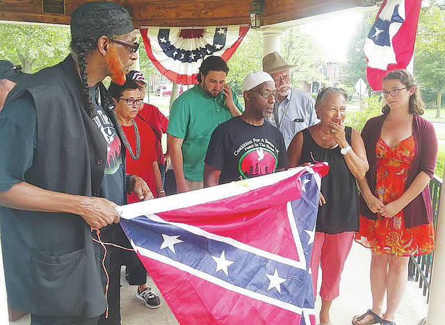 Members of the Fair Minded Coalition of Lorain County hold a symbolic decommissioning ceremony for the Confederate flag in downtown Wellington.