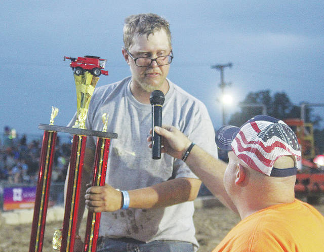 Joseph Knoble Jr. of Henrietta Township is handed a first place trophy Saturday during the Lorain County Fair's combine derby.
