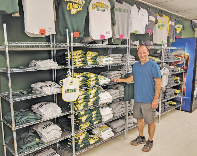 Darrell McCarty shows off the Amherst apparel being sold in the new Comet Corner at Dairy Mart on Cleveland Avenue.