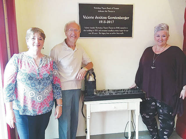 A plaque dedicating the Workshop Players Theater to founder Valerie Gerstenberger is unveiled Saturday by show director Pat Price, board president Dave Stacko, and theater director Dawn Watson.
