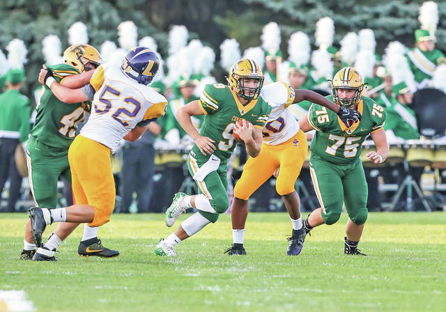 Comets quarterback Jimmy Schill scrambles free against Lakewood with the help of Russell Hellinger and Aiden Johnson.