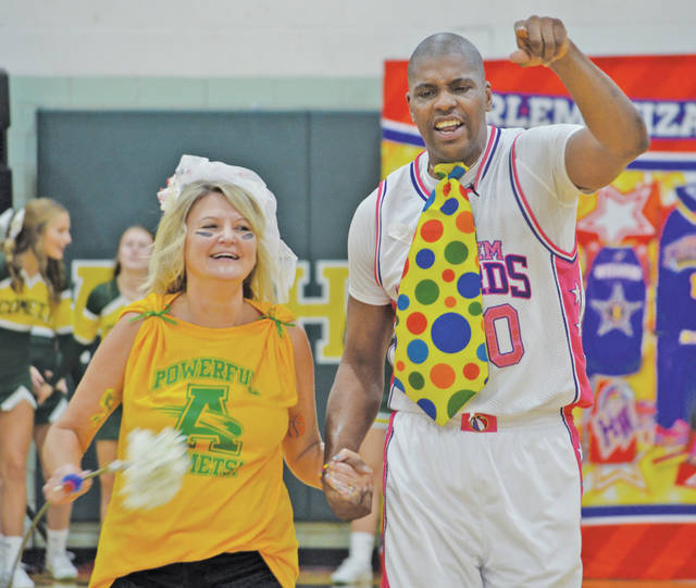 Teacher Nadine Wearsch meets Swoop at half-court Tuesday for an impromptu wedding ceremony after he proposed during a Harlem Wizards exhibition game at Steele High School — it was all part of the show!