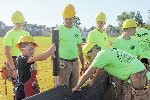 Nord Middle School third-grader Mason DiFlippo smiles as he helps drive a metal pole into the ground while Lorain County Junior Vocational carpentry seniors Taylor Poling, Bryson Baldwin, Angela Mazurek, and Doug Pritt supervise.