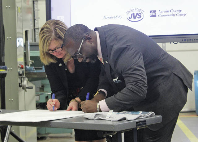 Lorain County Joint Vocational School superintendent Glenn Faircloth and Lorain County Community College president Marcia Ballinger sign a resolution, sealing a collaborative program to help JVS juniors earn credit toward an associates degree.