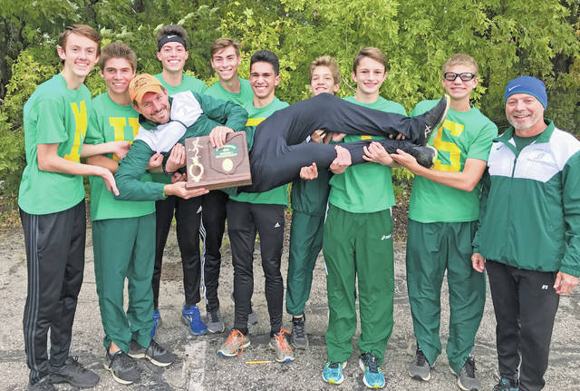 Cross country coach Rob Glatz is hoisted by his runners after the team took first place this weekend at the district championship.