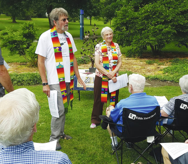The Revs. Steve and Mary Hammond, wearing rainbow-colored stoles, hold a service for the environment on Tappan Square.