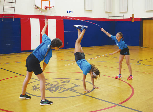 Saya Miyazawa and Helen Levy twirl two ropes while Zoe Stephens performs a trick during their double-Dutch freestyle routine.