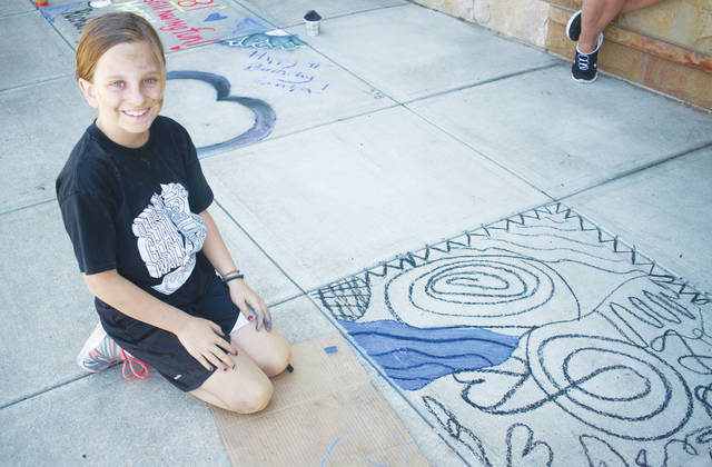 Alison Gott's abstract masterpiece covers not only the sidewalk, but her hands and face too.