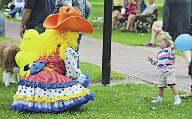 """One-year-old Elizabeth Perkins has her first encounter with a very colorful clown. Peppy, """"the official hug therapist,"""" passed out yellow and blue balloons all evening."""