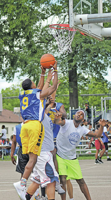 Sam Daniels of team Lakeside Inc. springs toward the hoop while opposing team Commodore tries to block the shot.