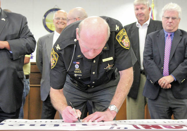 "Dep. Dennis Cavanaugh of the Lorain County Sheriff's Office signs on to a new ""Coalition of Partners"" approved by county commissioners July 31 to combat the area's opioid epidemic."