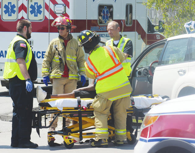 Oberlin firefighters and Central Lorain County Ambulance District EMTs treat one of two drivers involved in a crash Monday in New Russia Township.