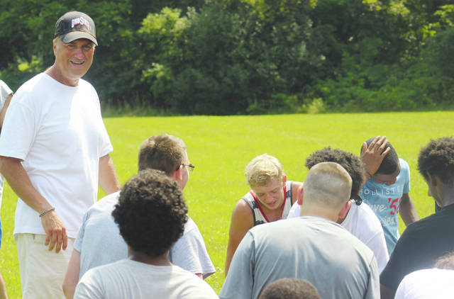 Coach Mike Akers shares a laugh with Oberlin Phoenix players after a practice session Aug. 3. He will try to guide the team to its first winning season since 2012 after a 29-year career that includes stops at Admiral King, Lorain High School, and Brookside.