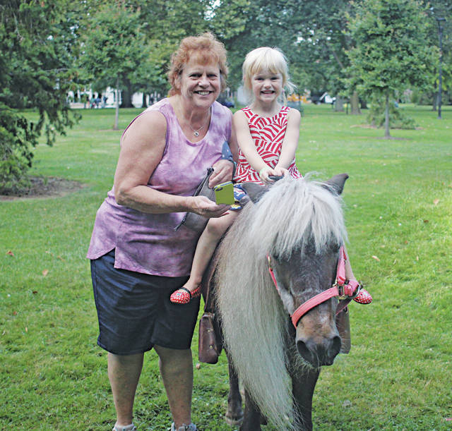 Becky Remo holds Jillian Smith atop a pony for a quick ride around Tappan Square.