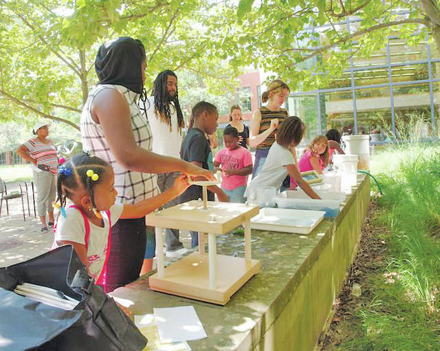 Students from the Harrison Cultural Community Centre and Oberlin build paper towers outside of the Science Center as part of a two-day camp.