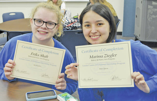 Bakery and pastry arts students Erika Shaft and Marissa Ziegler smile with their summer internship certificates of completion.