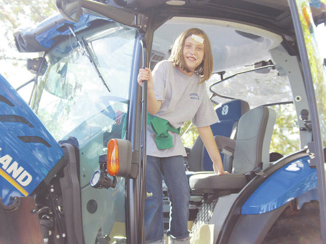 Lillian Mull, a fourth-grader at McCormick Middle School, take a look inside a tractor during this year's Food for America event at the Lorain County Fairgrounds.