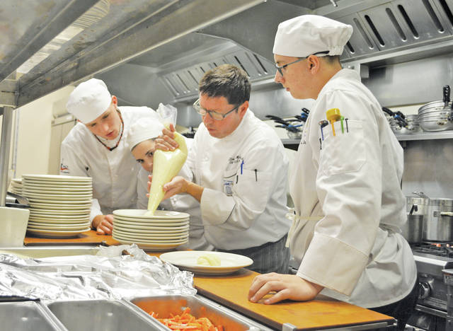 Chef Tim Michitsch demonstrates how to display potato puree on an entree plate to students David Chambers, Breanna Unger, and Robert Bowden.