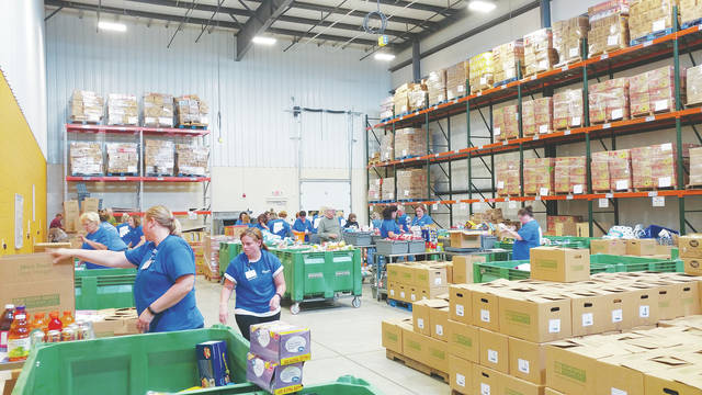 Nurses from the Cleveland Clinic in Avon sort through donated food at Second Harvest's food repackaging room.