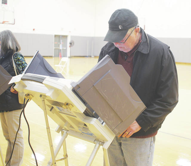 Bill County casts his ballot Tuesday at the Oberlin College Philips Gymnasium.