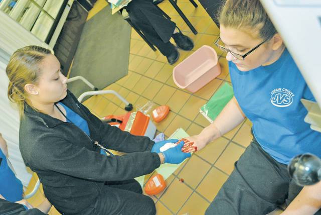 Junior Angelina Gonzalez of Wellington tends to the injuries of senior Hannah Morgan of Elyria during a mock disaster drill at the Lorain County JVS.
