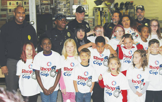 Oberlin police officers and area kids share a laugh Dec. 12 during the department's annual Shop With a Cop day. Kids were given $100 and picked Christmas gifts after being treated to snacks and a visit with Santa.
