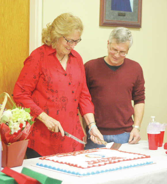 Sharon Soucy and Scott Broadwell slice into a cake to celebrate their 10-year tenure on council.