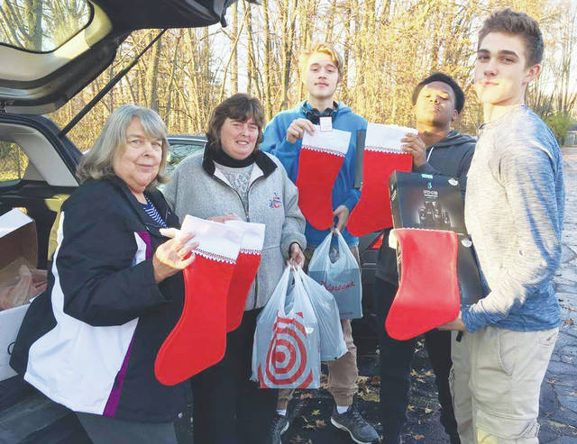 Julie Mullins, teacher Donna Shurr, and students from the Interact Club stuffed stockings with personal hygiene items.