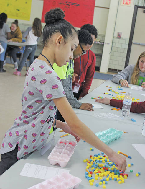 Sapporah Rodriguez fills an egg carton with colored cubes during a math challenge through the Fraction Club.