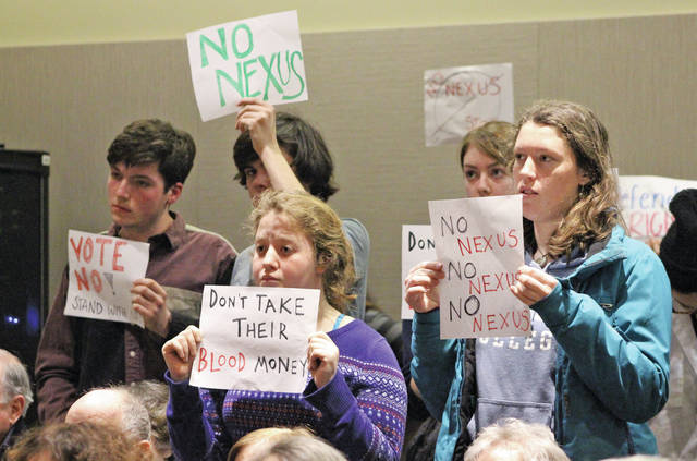 Members from Students for Energy Justice hold signs as Oberlin city council members contemplate their vote on the NEXUS settlement.