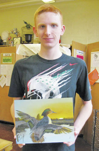 Ian Valerius shows his award-winning painting of a green-winged teal.