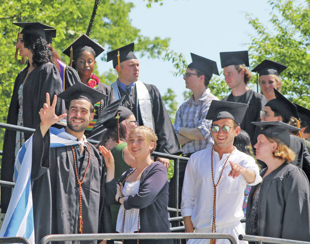 Graduates wave to family members as they prepare to walk onstage.