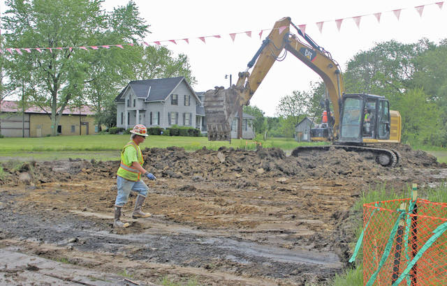 An excavator digs up a plot of land along Rt. 58 to build an accessway for NEXUS crew members.