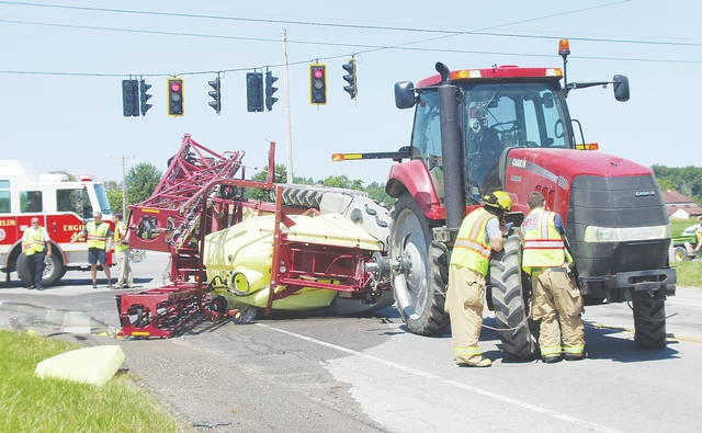 Oberlin firefighters clean up leaked fertilizer Friday after a tractor's tank turned onto its side at the corner of Rt. 58 and Russia Road.