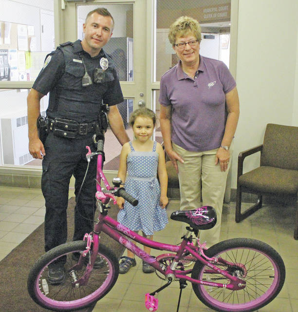 Patrol officer Adis Kuduzovic and AAA safety advisor Lori Cook present Adelaide Bandy with a brand new bike and helmet.
