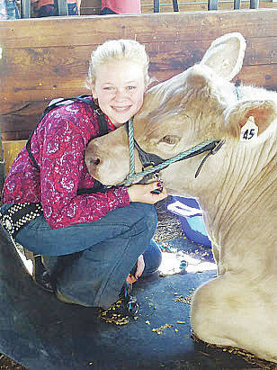 Kayler Frey of Avon hugs her cow, Triton, before he is sold in a livestock auction at the Lorain County Fair.