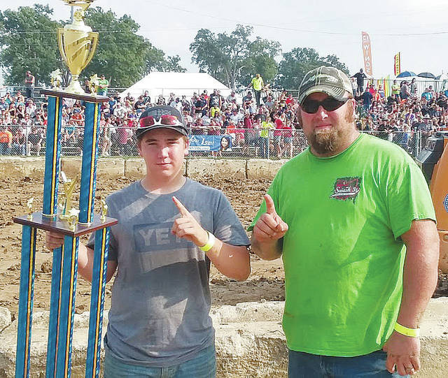 Kolby Smallwood of Marysville and family friend Jacob Gilliam celebrate a first place finish in Sunday's junior division demolition derby at the Lorain County Fair.