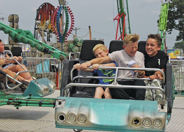 """Charlie Beverage, Brian Beverage, and Aiden Wohleber of North Ridgeville whip left and right on a ride called the """"Twister."""" Immediately after it ended, Wohleber jumped back into line and shouted, """"Let's go again!"""""""