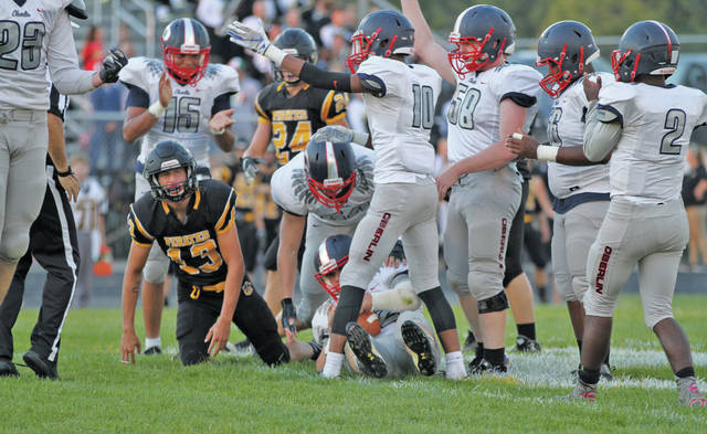 """Defensive back Aaron Arnold and junior linebacker Riley Horning signal """"Oberlin ball"""" as teammate Brendan McClung recovers a Black River fumble."""