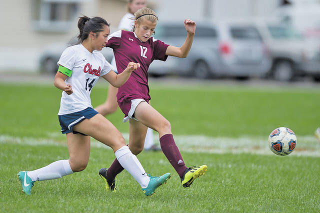 Oberlin's Rosy Turner clears the ball away before Wellington's Lauren Alley can get there.