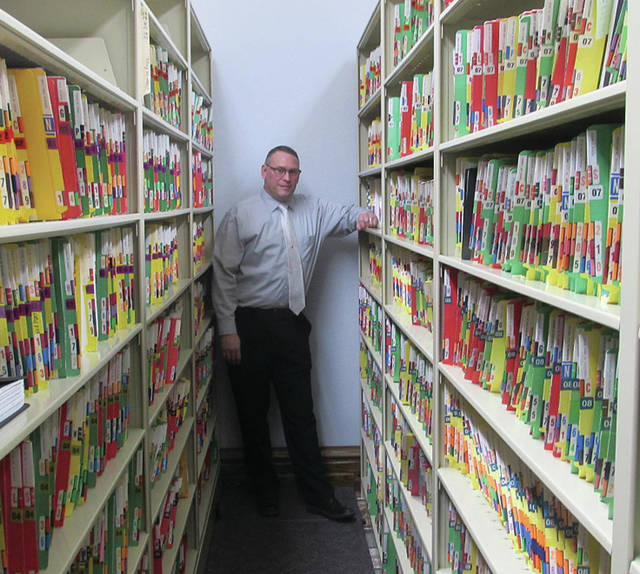 Fulton County Clerk of Courts Tracy Zuver stands among a fraction of the permanent records the county will transfer through a painstaking process to computer records over at least a 20-year period.