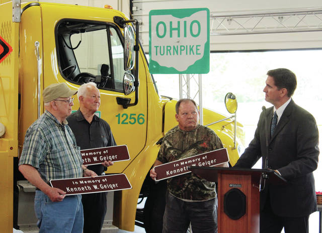 Randy Cole, Ohio Turnpike executive director, gave replicas of a Memorial Sign in honor of Kenneth W. Geiger to family members on Friday during a ceremony in Swanton.