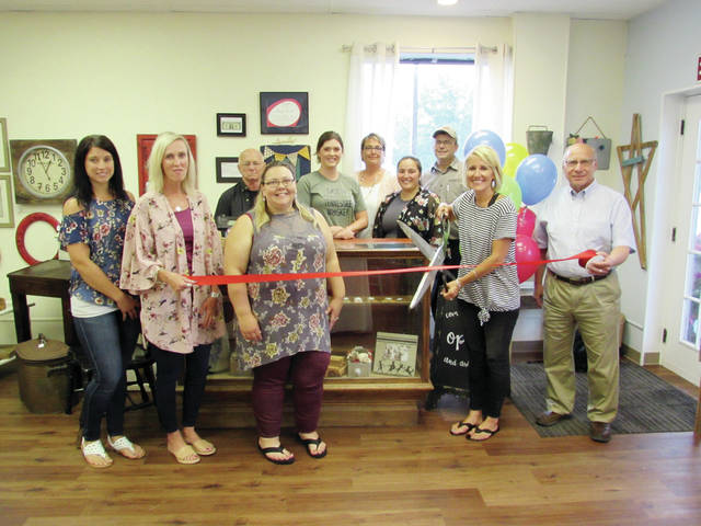 Owner Jenny Vonier cuts the ribbon at the grand opening of her downtown Wauseon shop, Junk & Disorderly, surrounded by her vendors and Chamber of Commerce members. Located at 245 N. Fulton St., the store features an eclectic assortment of merchandise, including hand-carved wood items, clothing, baby items, antiques, and refinished items. Hours are Thursday and Friday, 5-8 p.m., Saturday, 10 a.m.-1 p.m.