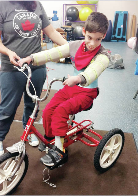 Christian Lee, a student at New Horizons Academy at Sara's Garden in Wauseon tries out one of four Rifton Adaptive Tricycles donated by the Toledo Community Foundation and the Toledo Mud Hens Baseball Club's Helping Hens Fund for special needs students.
